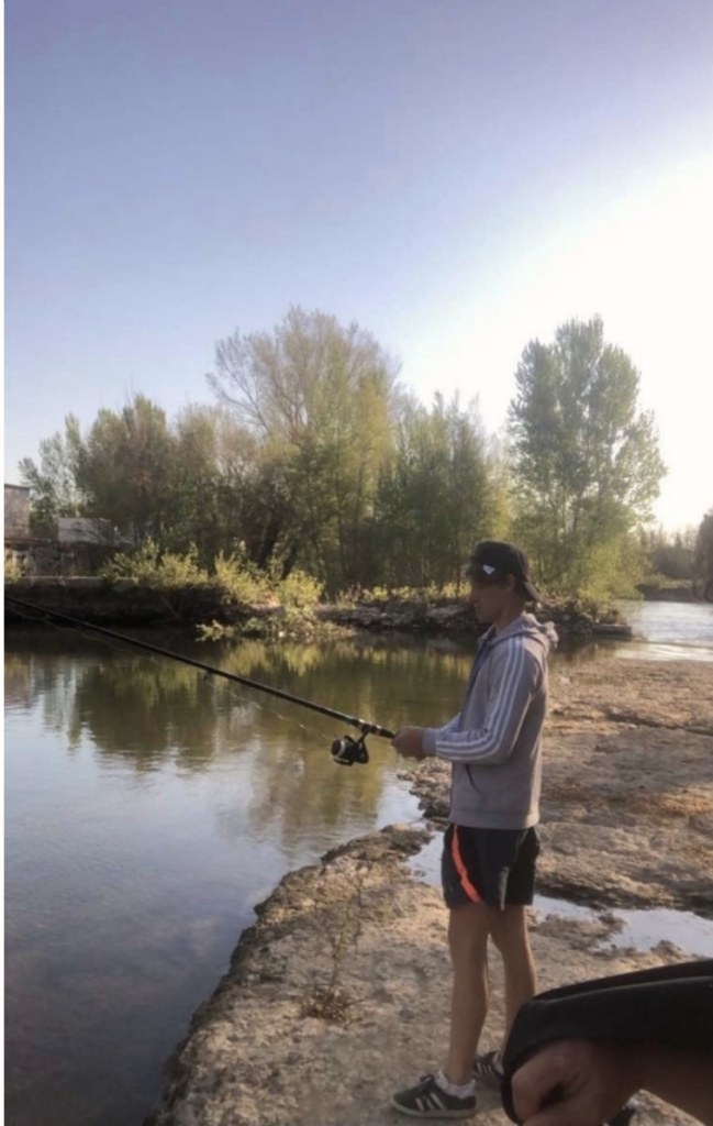 louis at the edge of a lake with a fishing pole